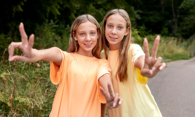 Gêmeos de frente fazendo o símbolo da paz