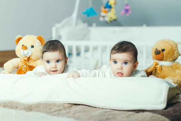 Gêmeos do bebê brincando na cama