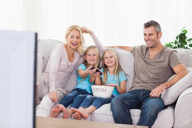 Gêmeos e pais assistindo televisão