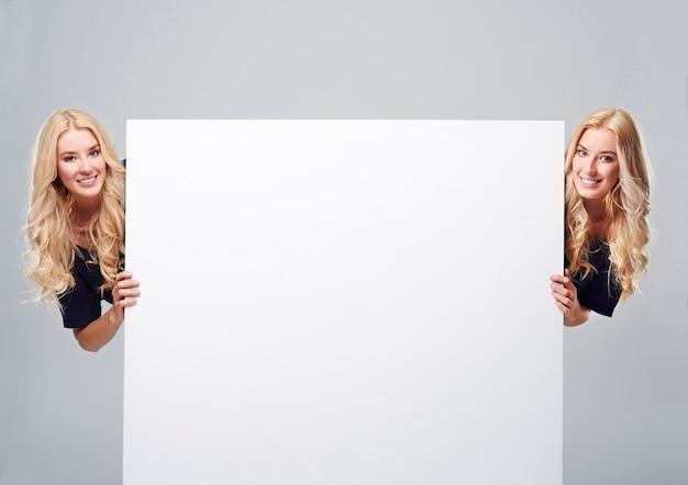 Gêmeos em ambos os lados do cartaz vazio