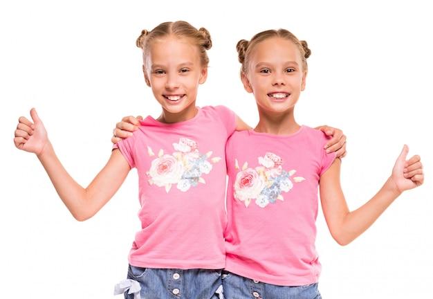 Gêmeos felizes que abraçam-se e que mostram os polegares acima.
