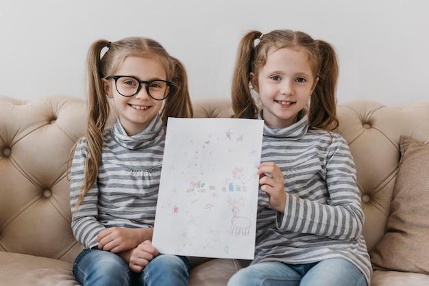 Gêmeos fofos segurando um desenho