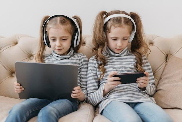 Gêmeos fofos usando dispositivos digitais