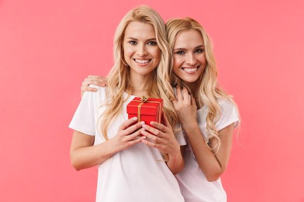 Gêmeos loiros felizes vestindo camisetas se divertindo com uma caixa de presente e olhando para a frente sobre a parede rosa
