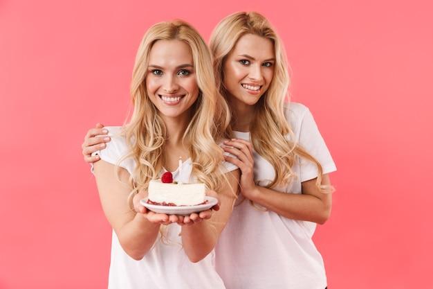 Gêmeos loiros sorridentes vestindo camiseta comemorando com bolo de aniversário e olhando para a frente sobre a parede rosa