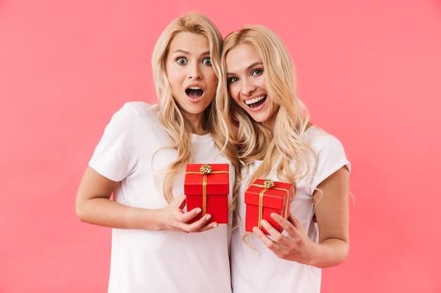 Gêmeos louros alegres vestindo camisetas segurando caixas de presente e olhando para a frente sobre a parede rosa