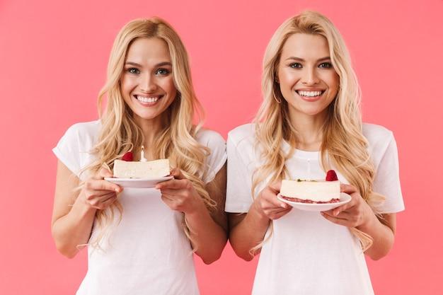 Gêmeos louros alegres vestindo uma camiseta comemorando com cheesecakes de aniversário e olhando para a frente sobre a parede rosa