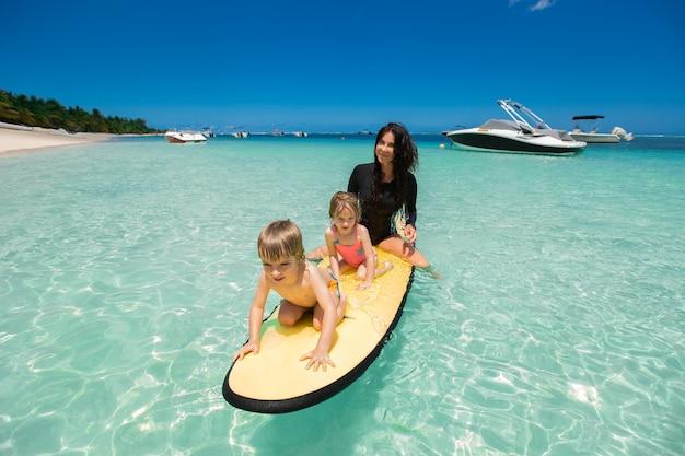 Gêmeos, menino e menina com a mãe surfando no oceano em um quadro negro