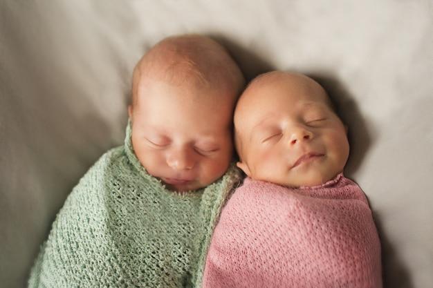 Gêmeos se abraçam. bebês recém-nascidos dormem juntos