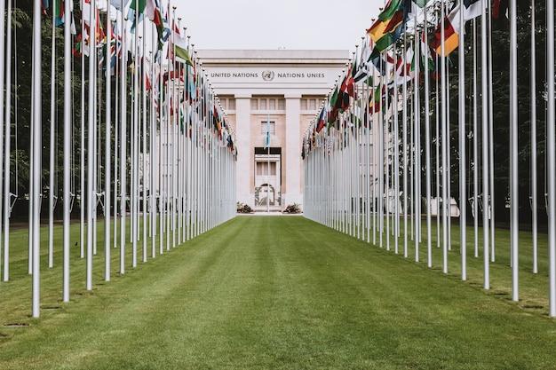 Genebra, suíça - 1 de julho de 2017: bandeiras nacionais na entrada do escritório da onu em genebra, suíça. a organização das nações unidas foi criada em genebra em 1947 e é o segundo maior escritório da onu