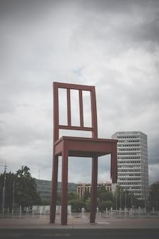Genebra, suíça - 1 de julho de 2017: cadeira quebrada na praça das nações em genebra em um lindo dia de verão com céu dramático, suíça, europa