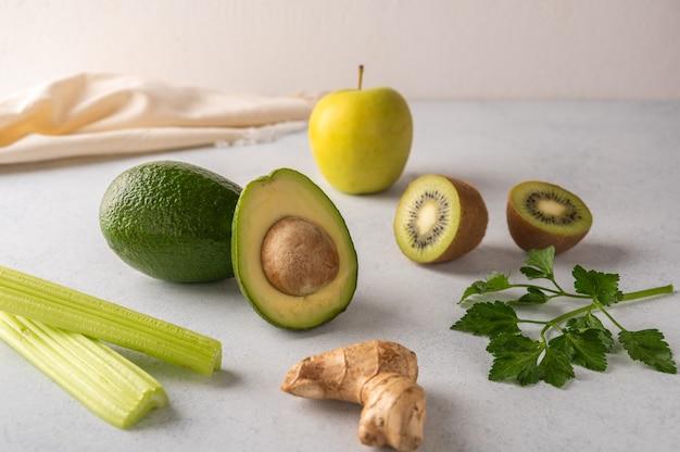 Gengibre, abacate, maçã, kiwi, aipo em um fundo claro