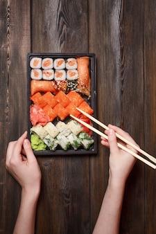 Gengibre, frutos do mar, mesa de madeira sushi e rolinhos deliciosos