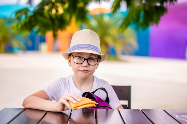 Gengibre menino de chapéu e óculos grandes, almoçando no parque