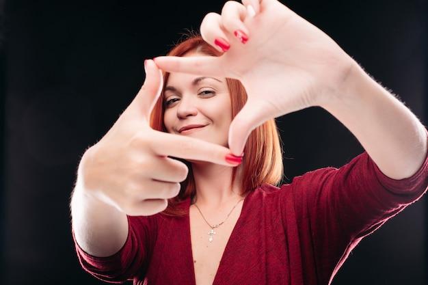 Gengibre mulher fazendo gesto de câmera com as mãos