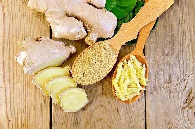 Gengibre ralado e moído em duas colheres de madeira, raiz de gengibre, folhas verdes na placa de madeira