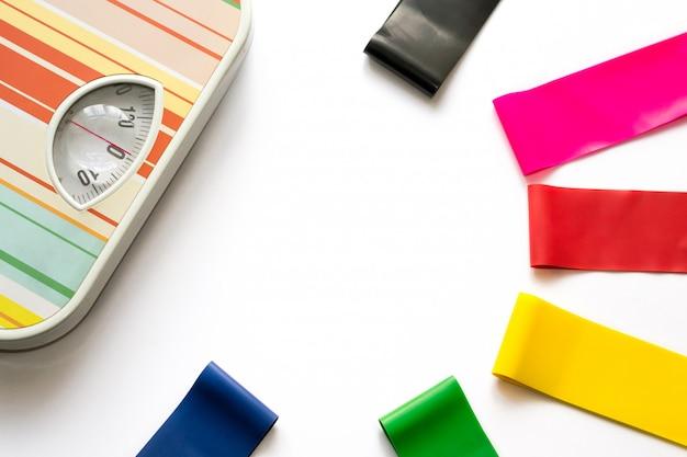 Gengivas de aptidão amarrado com fita métrica perto de balanças mecânicas coloridas