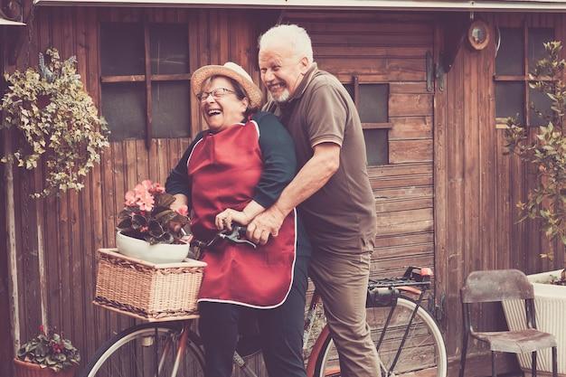 Gente caucasiana simpática aproveita o lazer ao ar livre tanto em uma única bicicleta, andando como um louco. juntos momentos engraçados em casa lá fora. filtros e cores vintage para um conceito alegre e divertido