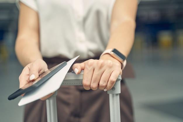 Gentil do sexo feminino mantendo as mãos no porta-malas enquanto espera o embarque