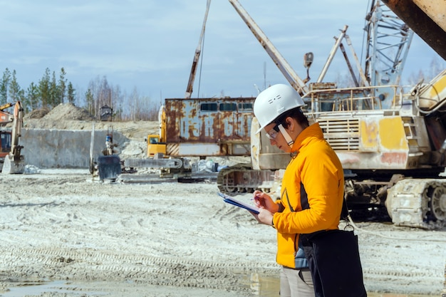Geóloga ou engenheira de minas escreve algo em uma caixa de mapa em meio a uma pedreira com equipamentos de construção