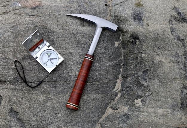 Geólogo bússola em pedras com martelo. conceito de ciência. martelo e ferramentas são dispostos em limalha