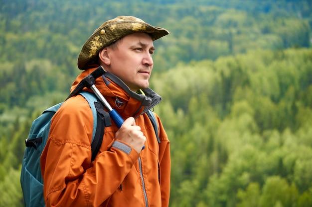 Geólogo masculino com uma mochila e um martelo geológico na mão contra a paisagem montanhosa
