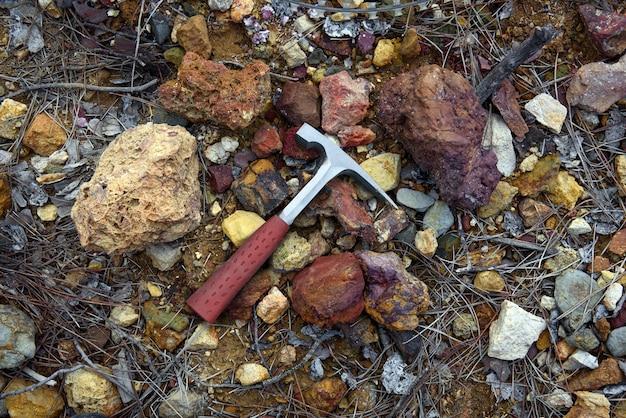 Geólogo rock pick sobre rochas coloridas vermelhas e amarelas ricas em minério de cobre e depósitos de sulfeto