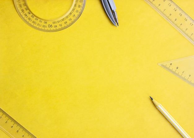 Geometria plana lay, réguas e compassos em um fundo amarelo, espaço de cópia