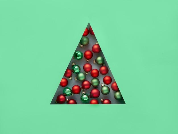Geométrico criativo natal plano leigos nas cores neo hortelã e vermelho. enfeites de natal no buraco triangular de papel em forma triangular de árvore de natal.