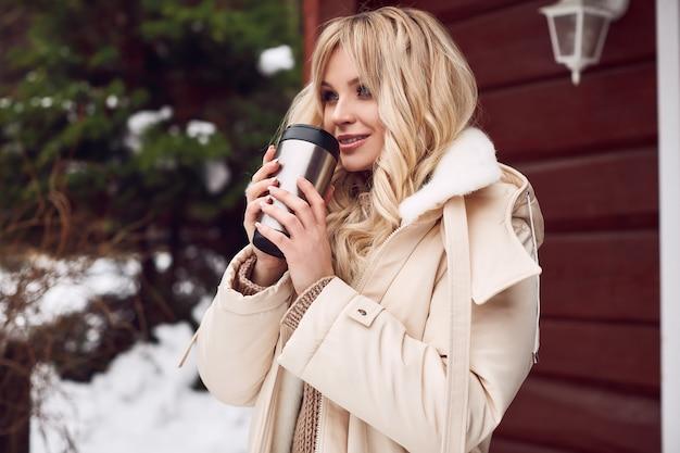 Georgeous loira elegante vestido brilhante com uma xícara de chá