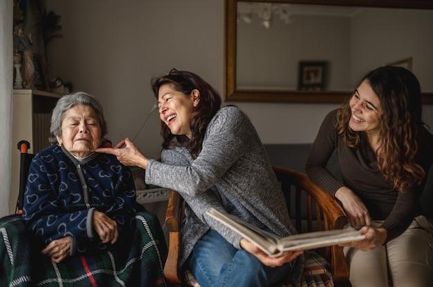Geração de mulheres com a velha avó doente sentada na cadeira de rodas e sorrindo, filha e neta, olhando um álbum de fotos.