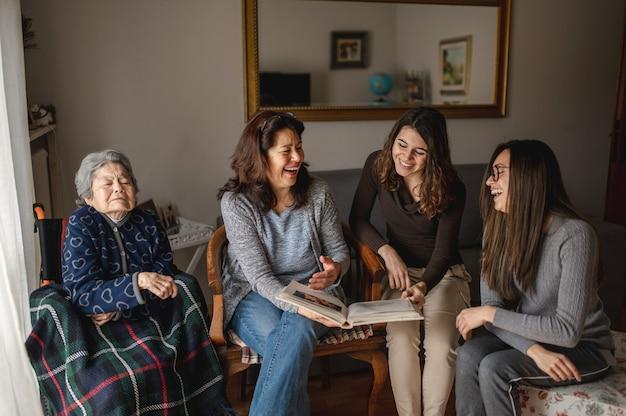 Geração de mulheres com avó idosa e doente sentada em uma cadeira de rodas ao lado da filha e das netas olhando um álbum de fotos