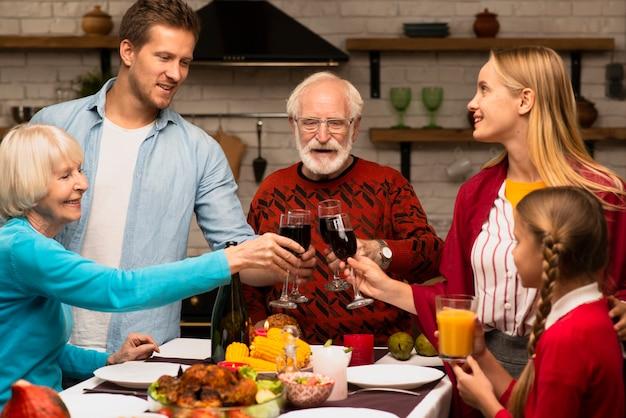 Gerações da família brindando copos no dia de ação de graças