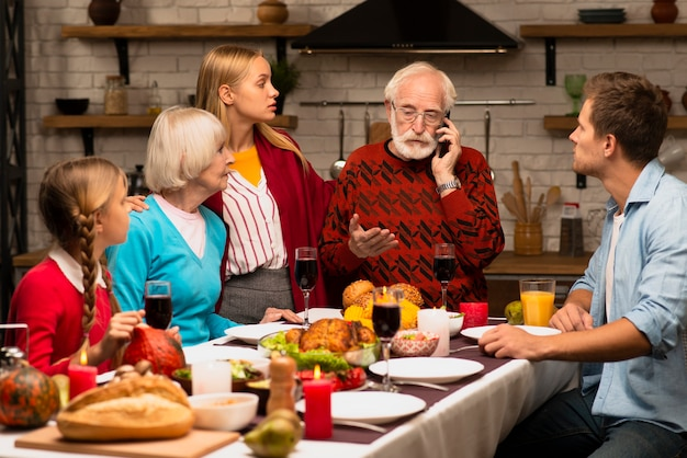 Gerações da família sendo curiosas e olhando para o avô
