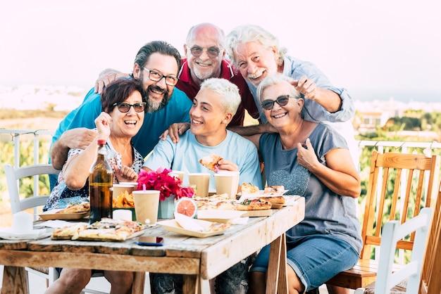 Gerações familiares aproveitam e comemoram com diversão, todos juntos rindo e sorrindo, posando para uma foto ao ar livre em casa