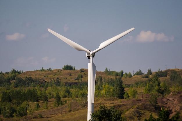 Gerador de poder do moinho de vento de encontro ao céu azul. fechar-se