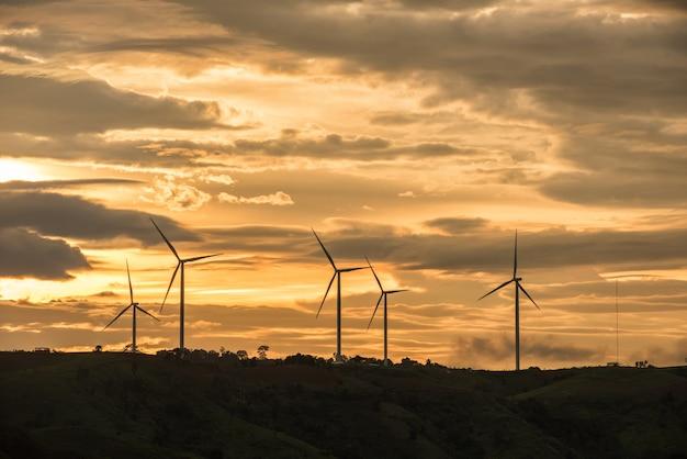 Geradores de energia de turbina de vento silhuetas por do sol na montanha
