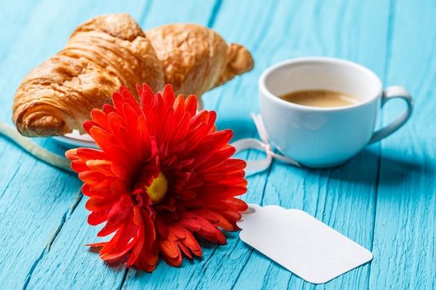 Gérbera, croissant, café, cartão postal vazio na mesa azul