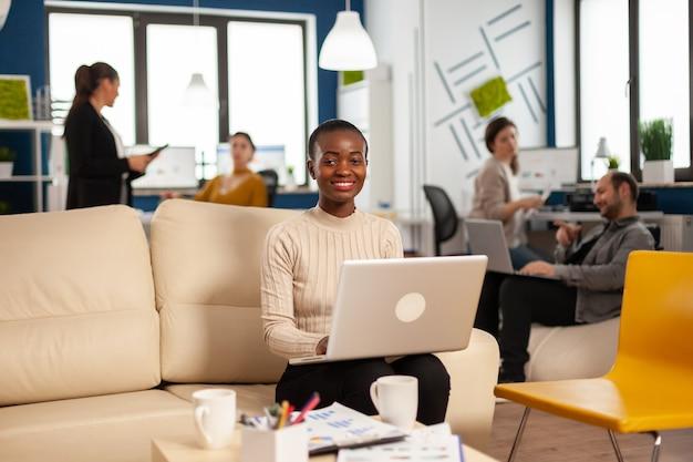 Gerente africana sentada no sofá em frente à câmera sorrindo enquanto a equipe trabalha em segundo plano com relatórios financeiros