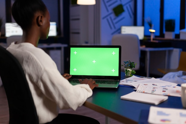 Gerente africano digitando em um laptop com visor de chroma key durante a noite no escritório de inicialização trabalhando horas extras