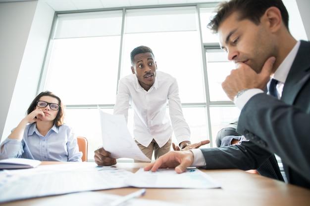 Gerente africano perguntando funcionários sobre erro na reunião