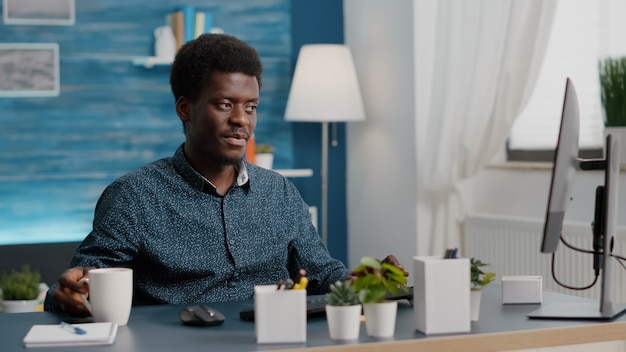 Gerente afro-americano trabalhando em casa, tomando café e digitando no computador