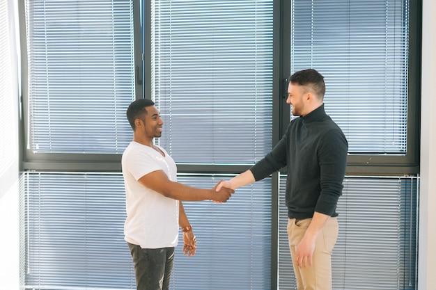 Gerente afro-americano, vestindo roupas casuais, aperta a mão do cliente homem ou cliente fazendo negócios em reunião de escritório pela janela. dois jovens empresários aperto de mão negócio de parceria de sucesso.