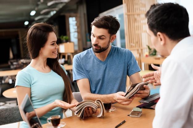 Gerente ajuda casal a escolher estofamento de móveis.