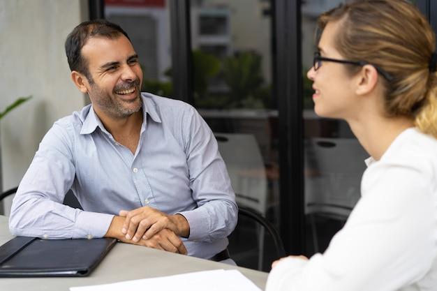 Gerente alegre médio da hora do adulto que tem a entrevista com o candidato