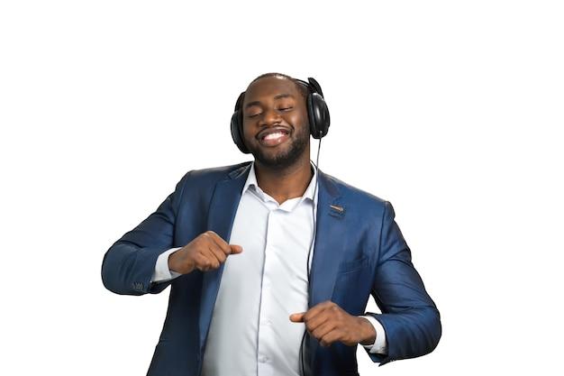 Gerente americano expressivo com fones de ouvido. bonito empresário negro ouvindo música e dançando no branco