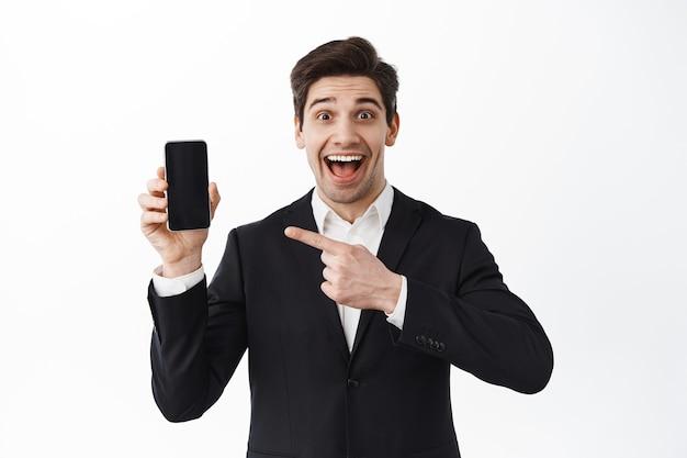 Gerente animado, trabalhador de escritório apontando para a tela do smartphone e sorrindo feliz, mostrando o aplicativo ou site, demonstrando o aplicativo, parede branca