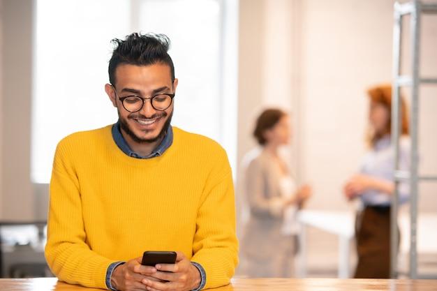Gerente árabe jovem bonito e positivo de óculos, parado no balcão do escritório e enviando mensagens de texto sms no telefone