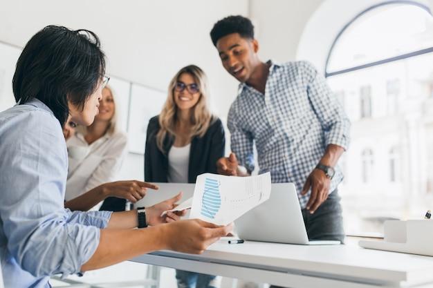 Gerente asiático em relógio de pulso sentado em seu local de trabalho e segurando papel com gráfico. retrato interno do programador africano de camisa quadriculada, falando com outros funcionários no escritório.