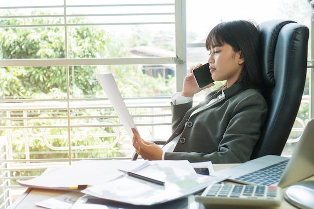 Gerente asiático novo da mulher de negócios que fala o smartphone, lendo originais dos relatórios dos originais